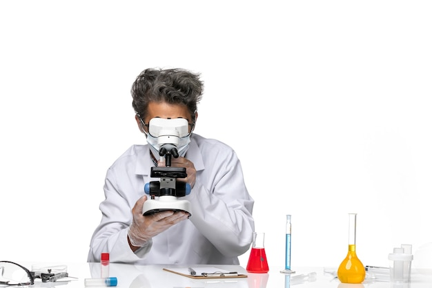 Front view middle-aged scientist in white medical suit holding microscope