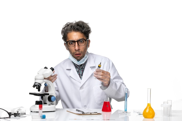 Front view middle-aged scientist in white medical suit preparing injection