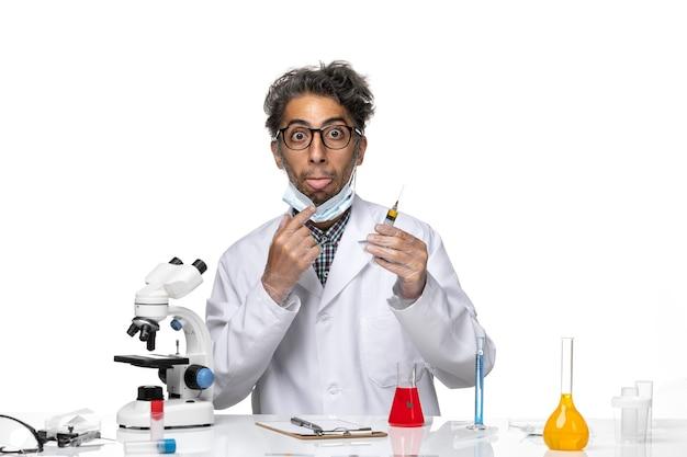 Scienziato di mezza età di vista frontale in vestito medico bianco che prepara l'iniezione