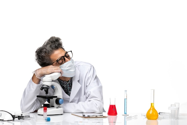 Front view middle-aged scientist in white medical suit sitting and sleeping with microscope