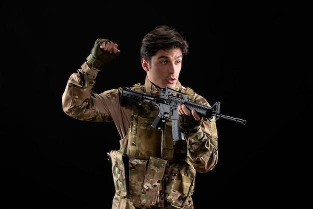 Vista frontale del militare in uniforme che punta il suo fucile in studio sulla scrivania nera