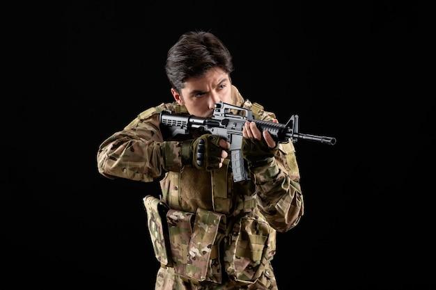 Vista frontale del militare in uniforme che punta il suo fucile in studio sul muro nero