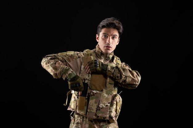 Vista frontale del militare in uniforme sulla parete nera