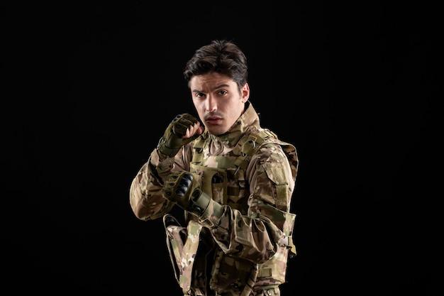 Vista frontale del militare in uniforme e posa del combattente sulla parete nera