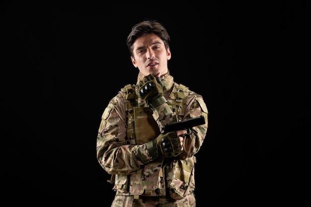 Vista frontale del militare in uniforme che tiene la pistola sul muro nero