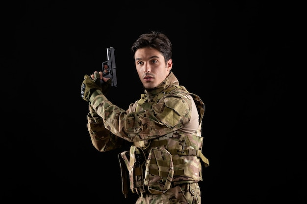 Vista frontale del militare in uniforme con la pistola sul muro nero