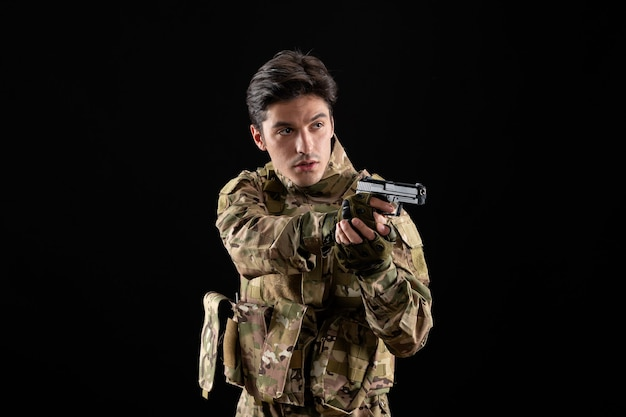 Front view of military serviceman in uniform with gun on black wall