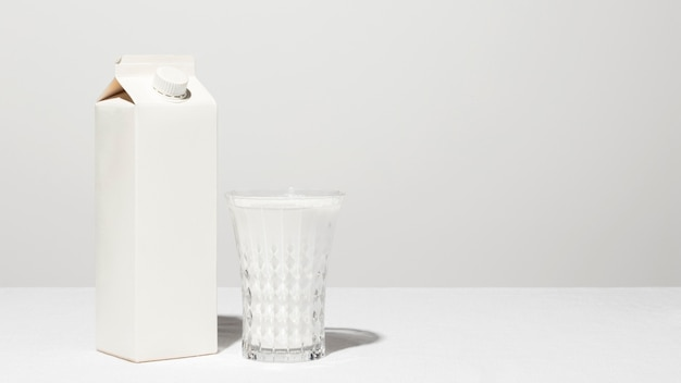 Front view of milk carton with full glass and copy space