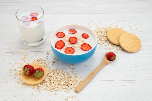 白、乳製品の朝食の健康に牛乳のガラスと一緒にイチゴとプレート内のオートミールと正面図牛乳
