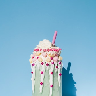 Front view of milkshake with blue background