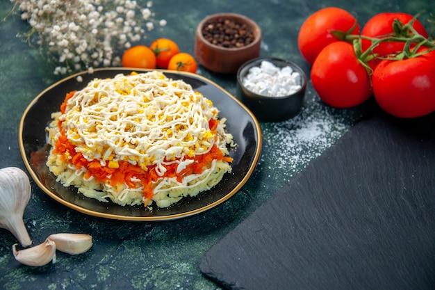 Vista frontale insalata di mimosa all'interno del piatto con condimenti e pomodori rossi sulla superficie blu scuro cucina foto cucina compleanno colore cibo vacanza pasto