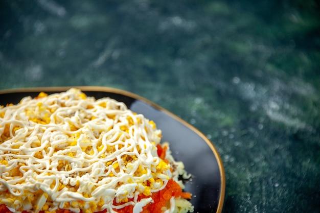 Vista frontale insalata di mimosa con uova patate e pollo all'interno della piastra sulla superficie blu scuro cucina festa compleanno cibo foto cucina colore