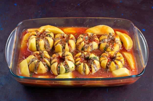 На темно-фиолетовом столе, вид спереди, из фарша внутри картофеля готовилась восхитительная еда.