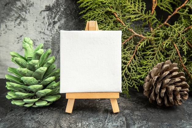 Front view mini canvas on wooden easel pine branch pinecones on grey background