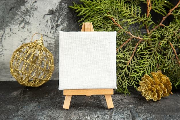 Vista frontale mini tela su cavalletto in legno rami di pino ornamenti natalizi su sfondo grigio