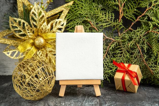 Mini tela vista frontale su cavalletto in legno rami di pino ornamenti natalizi su grigio
