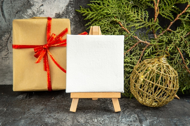 Vista frontale mini tela su cavalletto in legno ramo di pino ornamenti natalizi mini regalo su grigio