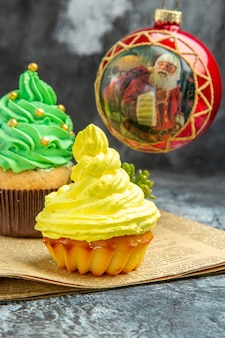 Front view mini colorful cupcakes red xmas tree ball on newspaper on dark new year photo