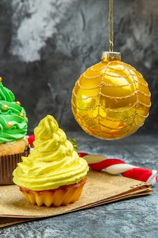 Vista frontale mini cupcakes colorati albero di natale palla caramelle di natale sul giornale al buio