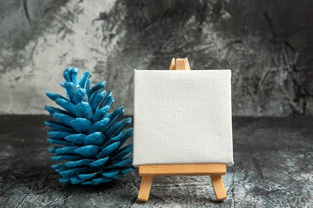 Vista frontale mini tela bianca con cavalletto in legno pigna blu su fondo scuro