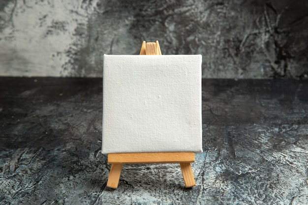 Front view mini white canvas with wooden easel on dark isolated background
