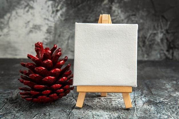 어두운 배경에 나무 이젤 빨간색 솔방울이 있는 전면 보기 미니 흰색 캔버스
