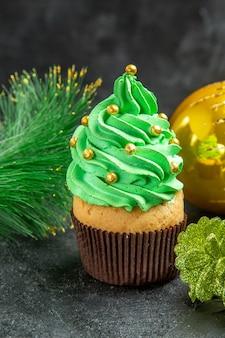 暗い孤立した背景の正面図ミニクリスマスツリーカップケーキとクリスマスの詳細