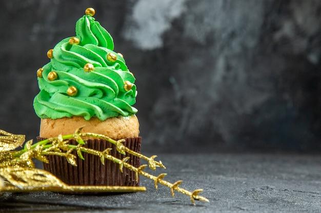 Vista frontale mini cupcake albero di natale e ornamento dorato appeso su sfondo scuro