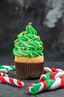 Front view mini xmas tree cupcake and xmas candies on dark background