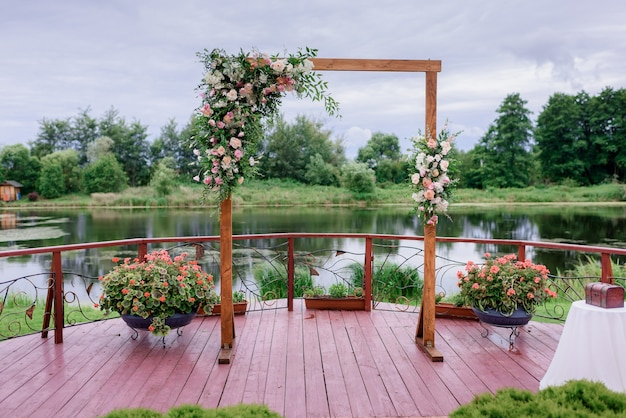 Front view of minimalist wooden arch decorated with flowers and greenery stands on the lake background