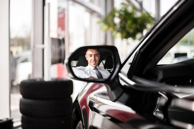 Vista frontale che rispecchia l'uomo dentro l'automobile