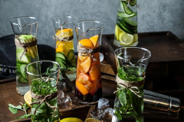 フロントビューミントレモンリンゴとキュウリとデカンターでデトックス水を混ぜる