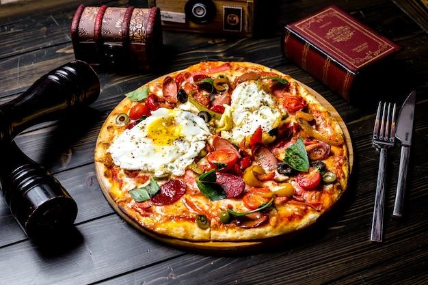 Front view mixed pizza with tomatoes olives bell pepper eggs sausages on the board a book a knife and a fork on the table