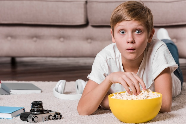 Front view of modern boy eating popcorn