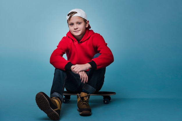 Front view of modern boy sitting on skateboard