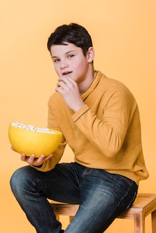 Front view of modern boy with popcorn