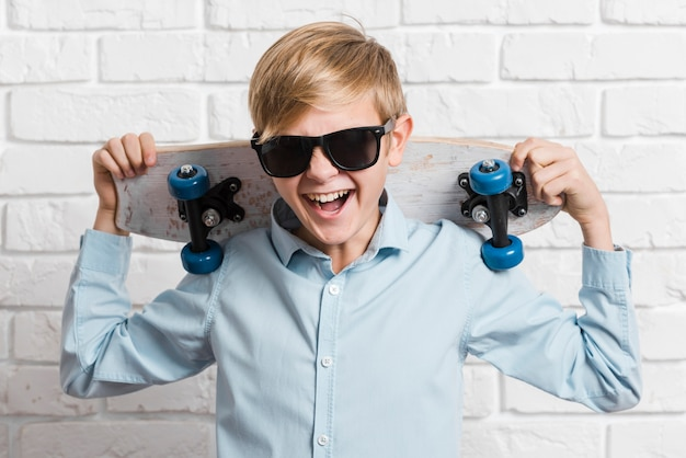 Front view of modern boy with skateboard and sunglasses