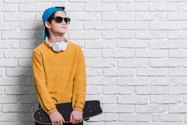 Front view of modern boy with skateboard with copy space