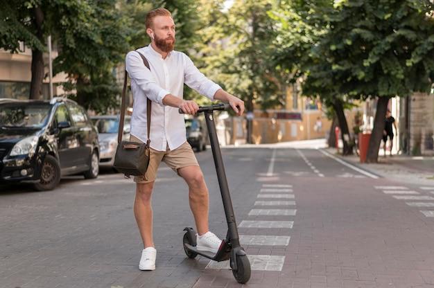Uomo moderno di vista frontale su scooter all'aperto