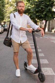 Uomo moderno di vista frontale su scooter all'esterno