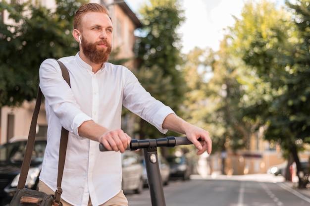 Uomo moderno di vista frontale su scooter con lo spazio della copia
