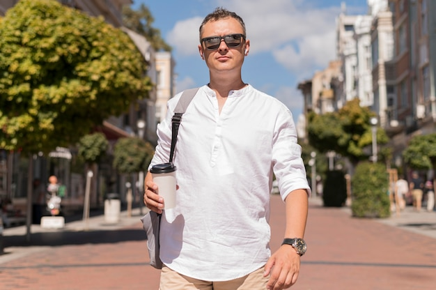 Front view modern man walking while holding a cup of coffee