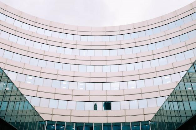 Vista frontale di un moderno grattacielo con finestre rosa e blu sotto un cielo grigio