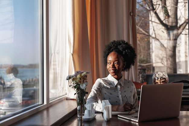 Вид спереди современная женщина за столом работает на своем ноутбуке