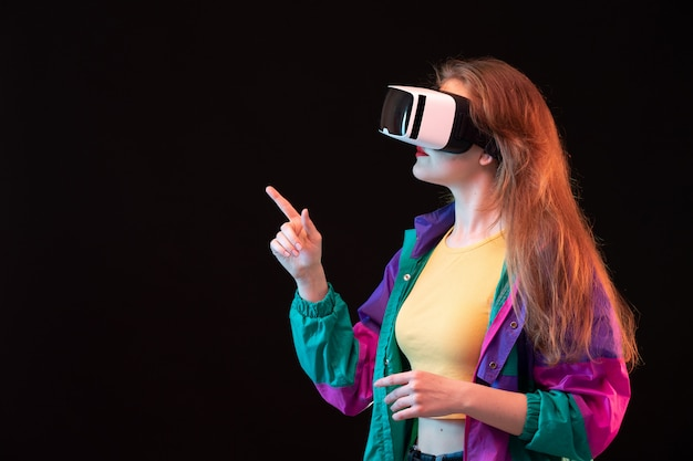 A front view modern young lady in colorful coat orange t-shirt playing and trying vr on the black background gaming interactive play