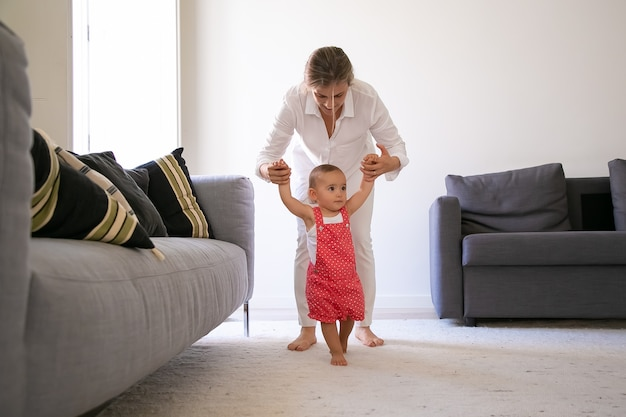 Vista frontale della mamma che tiene le mani della bambina e aiuta a camminare. neonata sveglia a piedi nudi in pantaloncini salopette rosse che imparano camminando nel soggiorno con l'aiuto della madre. tempo per la famiglia e concetto del primo passo