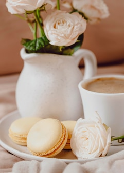 Front view of morning coffee with roses and macarons
