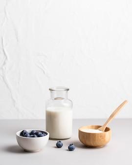 Vista frontale del latte del mattino con mirtilli freschi