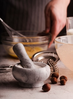 Front view of mortar and pestle with chestnuts and defocused cook