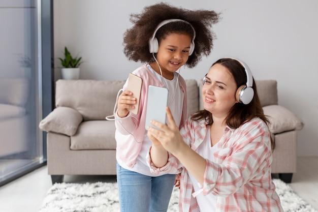 正面の母と娘が家で音楽を聴く